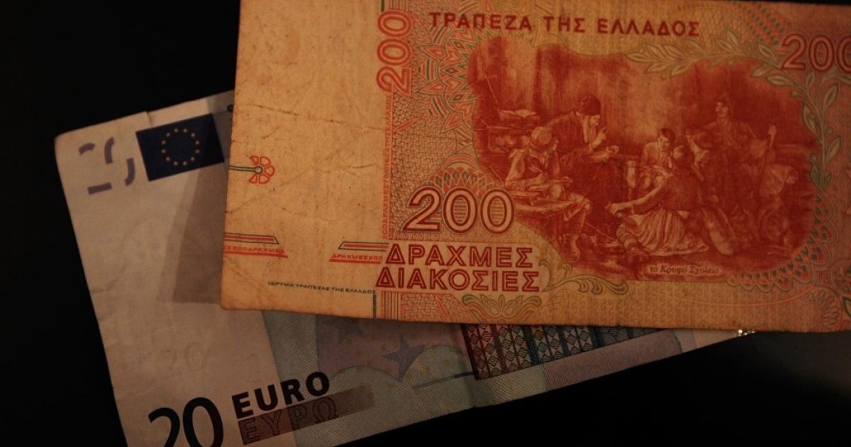 An old Greek drachma bill is seen on top of modern Euro note.</p>