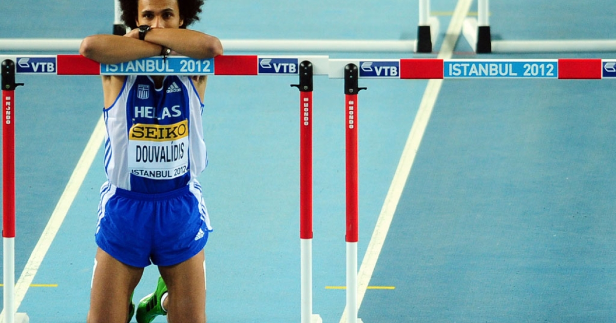 Greece's Konstantinos Douvalidis rests on a hurdle after a false start by another runner at the IAAF World Indoor Athletics Championships in Istanbul on March 10, 2012.  Due to deep funding cuts, Greece's athletics federation suspended domestic competitions and said international events are in jeopardy.</p>