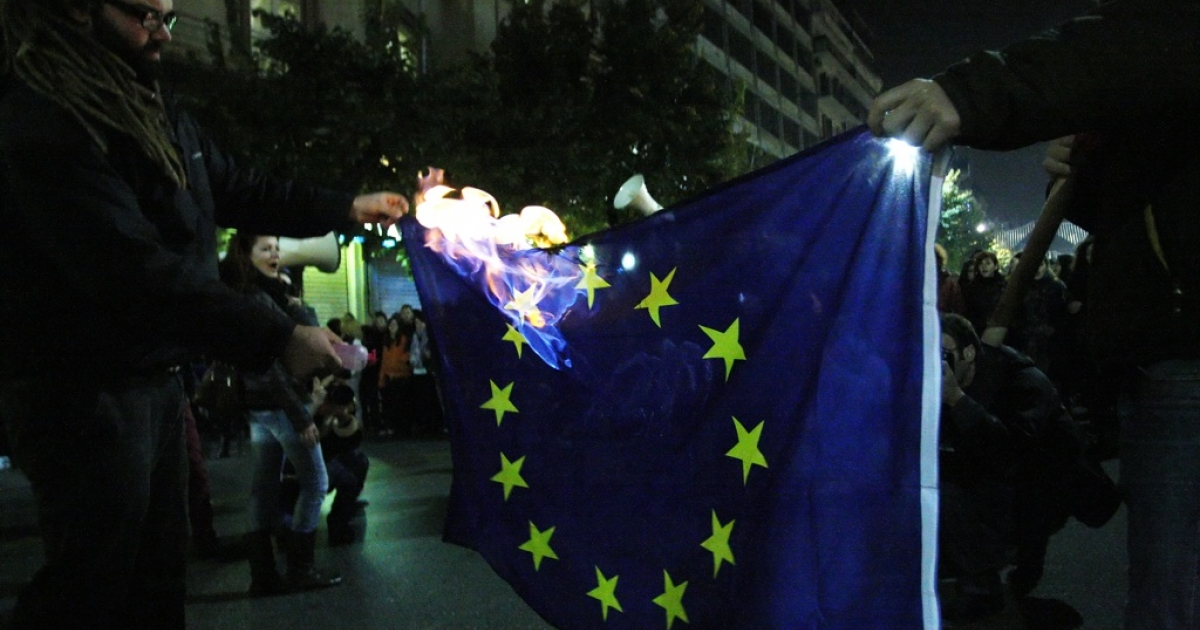 Demonstrators burn an EU flag during a protest in Thessaloniki on November 17, 2011 against austerity measures demanded by the new unity government to persuade its creditors to release bankruptcy-saving loans. Greeks are draining local banks in favor of Swiss accounts, London property and cash stashed in home safes.</p>
