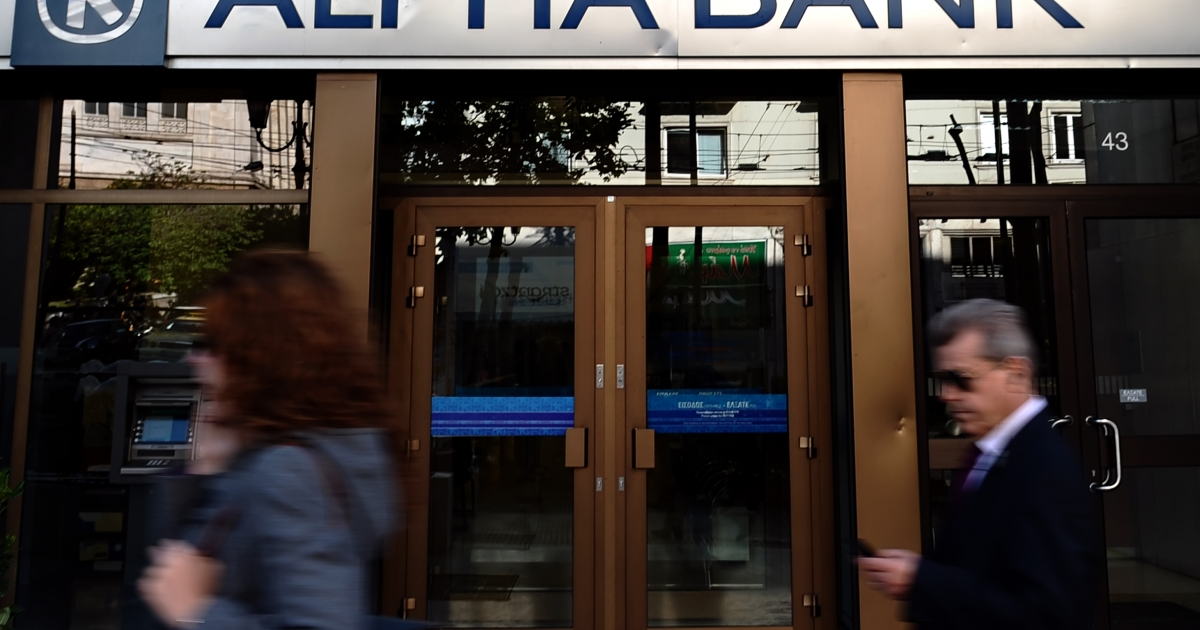 People walk outside an Alpha bank branch in Athens on April 19, 2012. Greek banks have been coming under increased pressure this week as consumers have been draining their accounts.</p>
