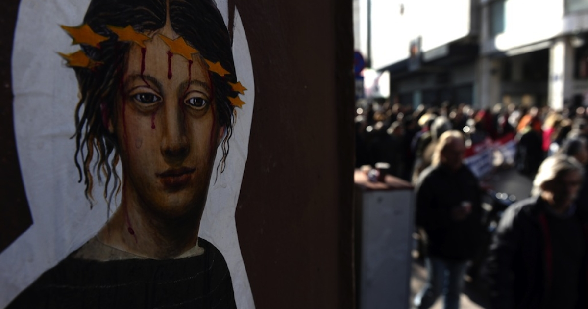Wall art is pictured next to demonstrators during a 24-hour strike against austerity measures in Athens on Jan. 17, 2012.</p>