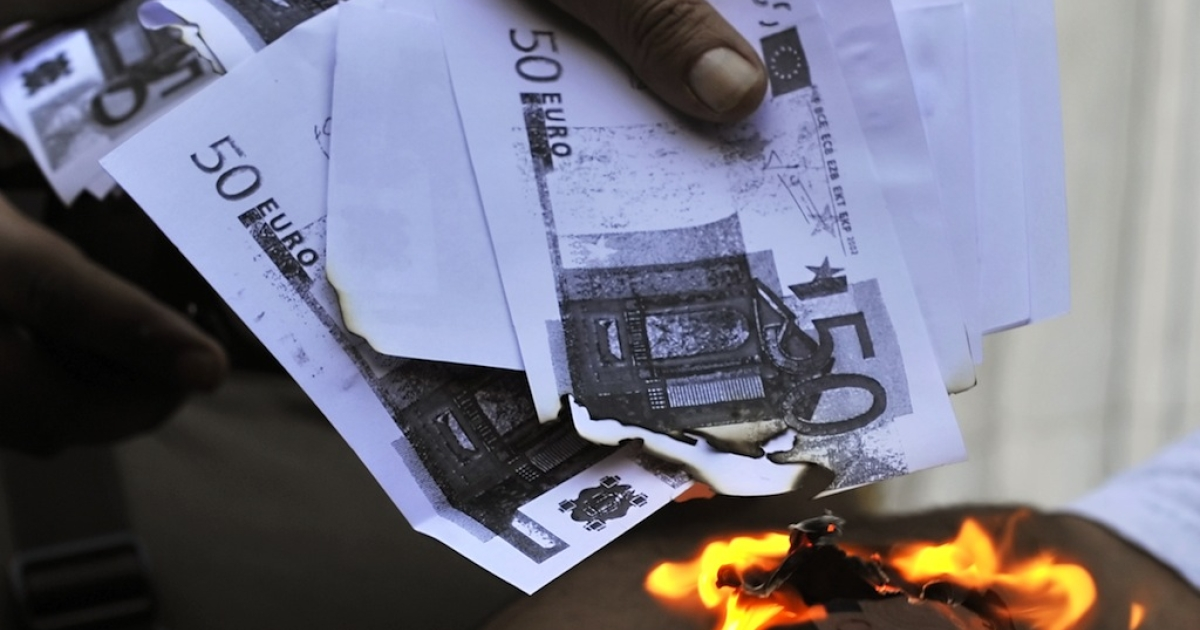 A protester sets fire to copies of euro notes in Athens. Many Greeks are angry over the austerity measures their government has imposed to secure bailout funds.</p>