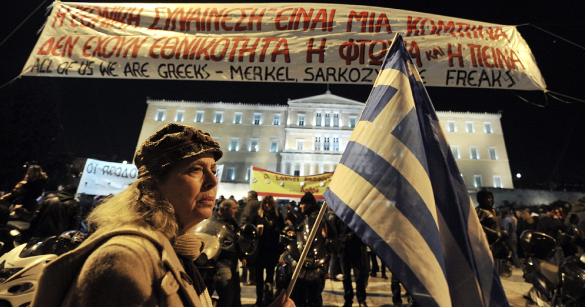 A woman holds a Greek flag as she takes part in a demonstration against new austerity measures recently approved by the government, in front of the Parliament in Athens, on February 19, 2012. Greek unions and leftist parties lead fresh anti-austerity protests on the eve of a meeting of eurozone finance ministers in Brussels called to approve a $170 billion loan package needed for Athens to avoid default.</p>