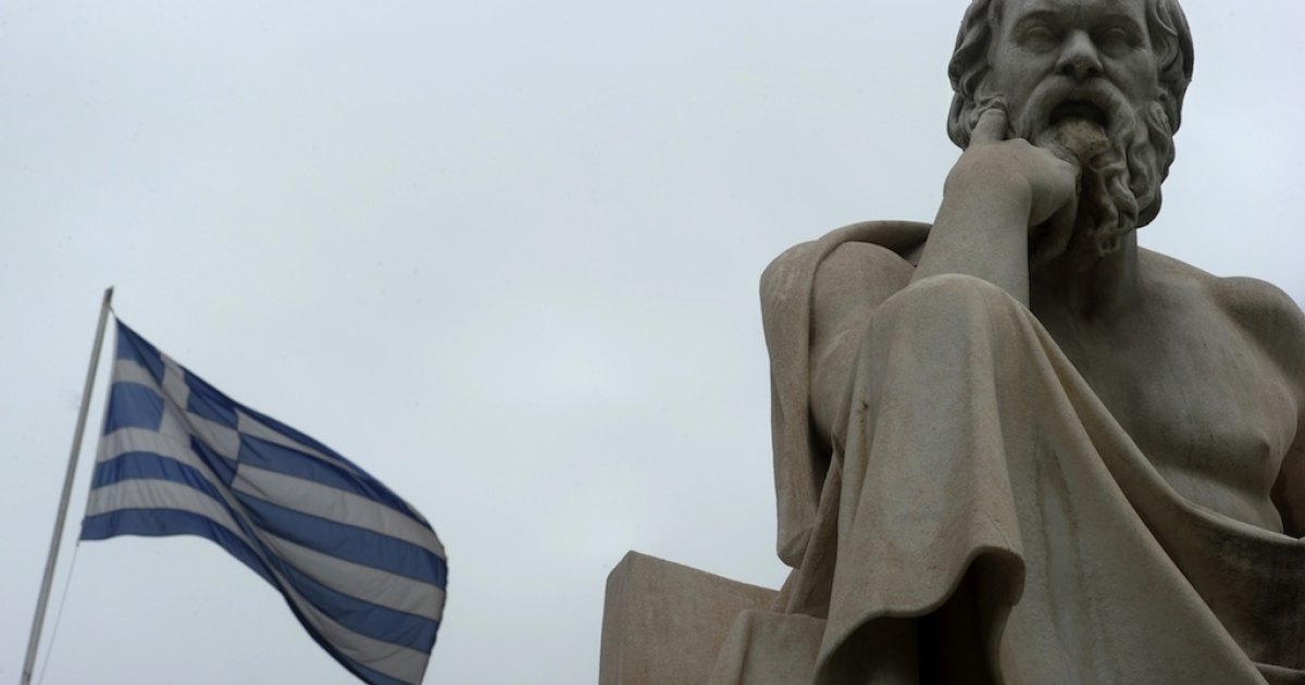 A Greek flag flies next to a statue of ancient Greek philosopher Socrates in the center of Athens.</p>