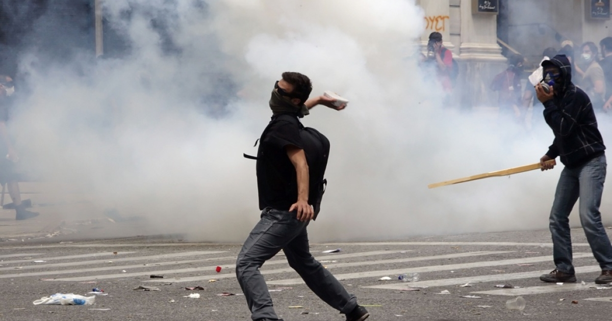 A demonstrator throws a stone at riot police during a protest against plans for new austerity measures June 15, 2011 in Athens, Greece.</p>