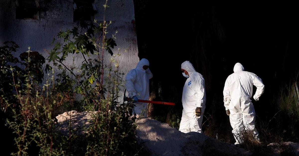 Forensics experts examine the makeshift grave in Guadalajara.</p>