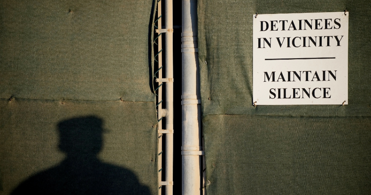 A soldier next to a sign at the US Naval Station in Guantanamo Bay, Cuba.</p>