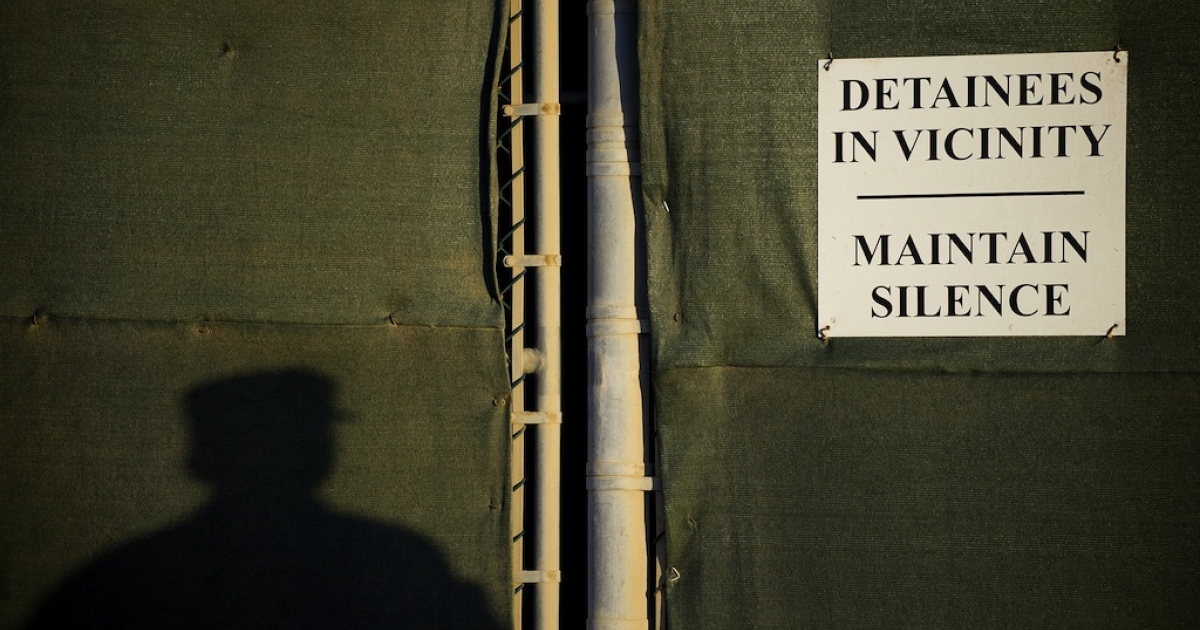 This picture shows a shadow of a US soldier next to a placard on a fence at the Guantanamo Bay detention camp.</p>
