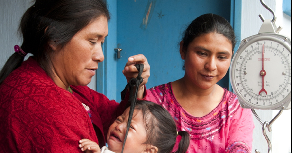 Alejandra Gonzales, a mother leader in the mostly indigenous community of Vixben, in the Western Highlands of Guatemala, holds 3-year-old Veronica Mendez as she tries to weigh her. Veronica was severely underweight for her age.</p>