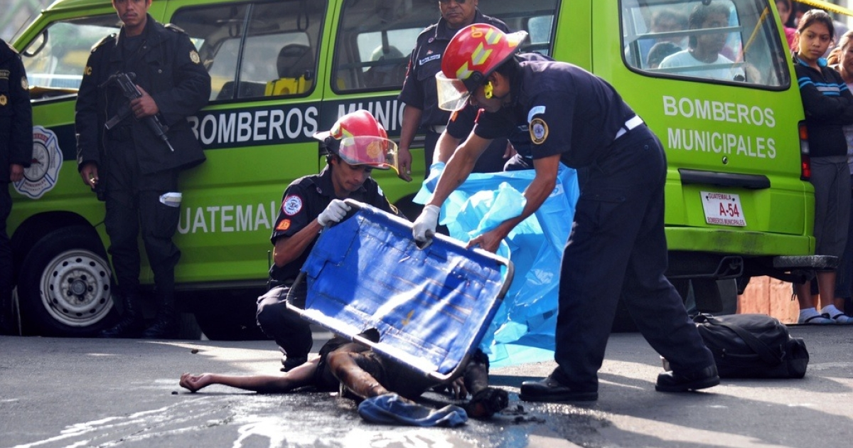 Firemen cover the corpse of a supposed hired assassin in Guatemala City on Sept. 1, 2010.</p>