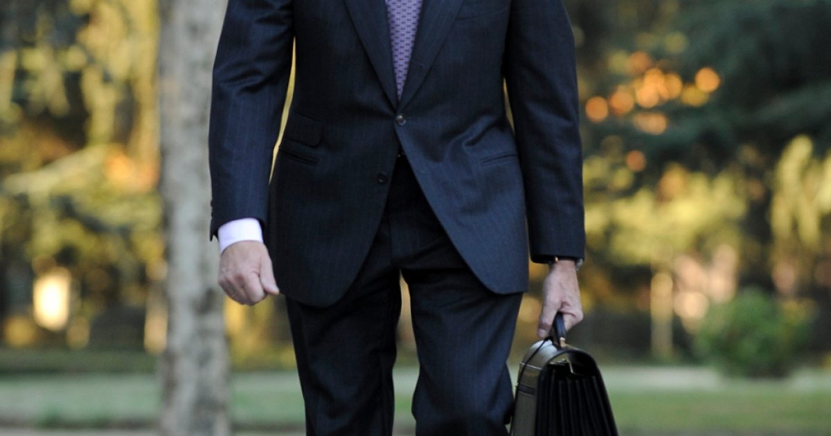 It's a tough job but somebody has to do it.  Luis de Guindos arrives for his first day of work as Spain's Economy Minister</p>