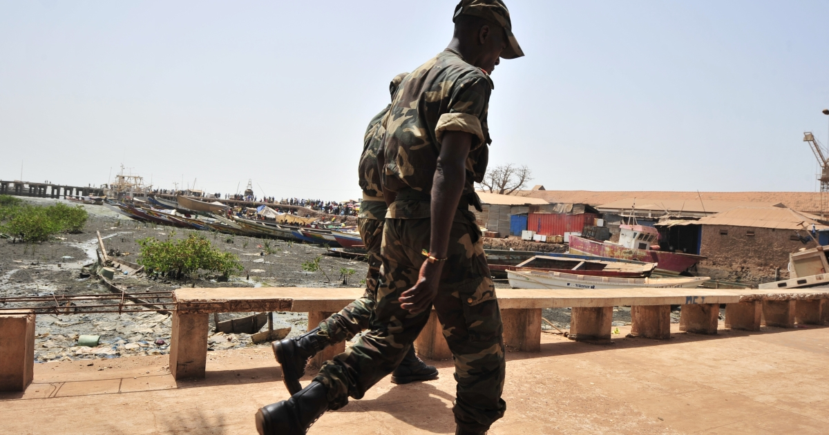 Soldiers walk on a bridge in Bissau on March 19, 2012 as officials tally the votes of the presidential elections.</p>