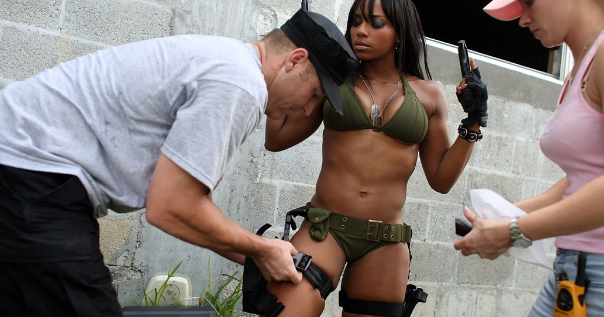 Producer Jason Atkins helps Mia Lawrence with a holster as she prepares to film a scene on the set of Girls and Guns, a web-based reality show featuring women shooting weapons. Some clothing lines have developed more subtle