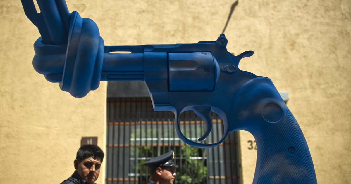 Mexican policemen walk by a sculpture of a knotted gun in Mexico City.</p>