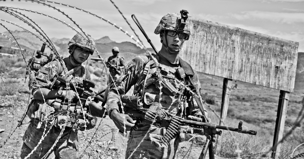 Pfc. Gary McClintock (left) and Pfc. Noah Nowell leave Combat Outpost Baylough on a patrol.  Nowell carries a M240B machinegun and 100 rounds.  In addition to his own weapon and ammunition, McClintock carries 1,000 M240B rounds and a spare barrel.</p>