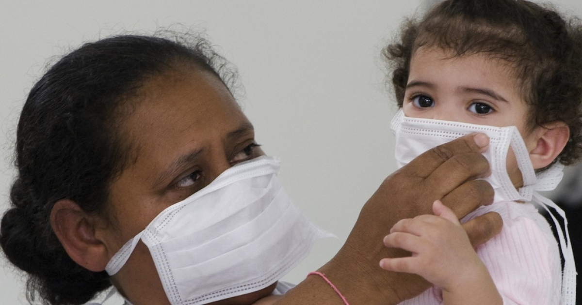 A woman puts a mask on her daughter as they wait to be checked for Influenza A (H1N1) (swine flu) infection at a special facility of the Miguel Couto hospital in Rio de Janeiro, Brazil, on August 6, 2009.</p>