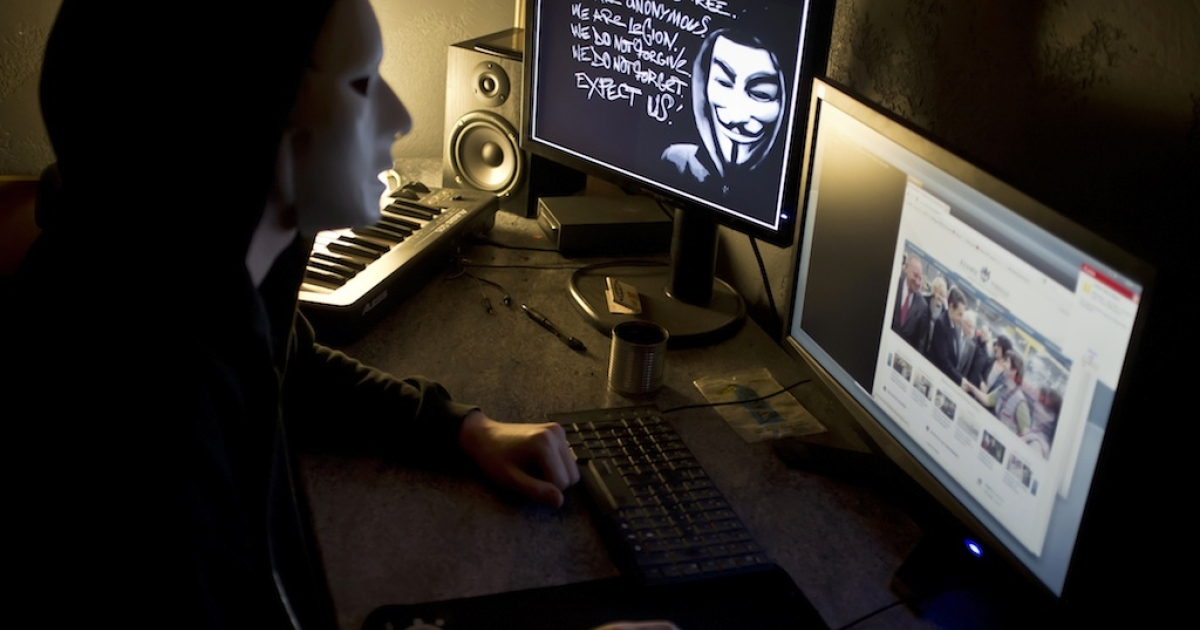 A masked hacker, who belongs to the Anonymous group, hacks the French presidential Elysee Palace website on January 20, 2012 near the eastern city of Lyon.</p>