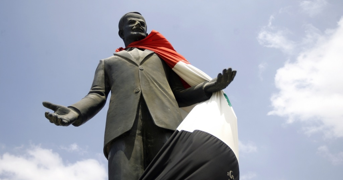 A Syrian flag hangs over a statue of the late president Hafez al-Assad on Aug. 30, 2011, near Homs. Alawites have ruled Syria since Hafez seized power in 1970.</p>