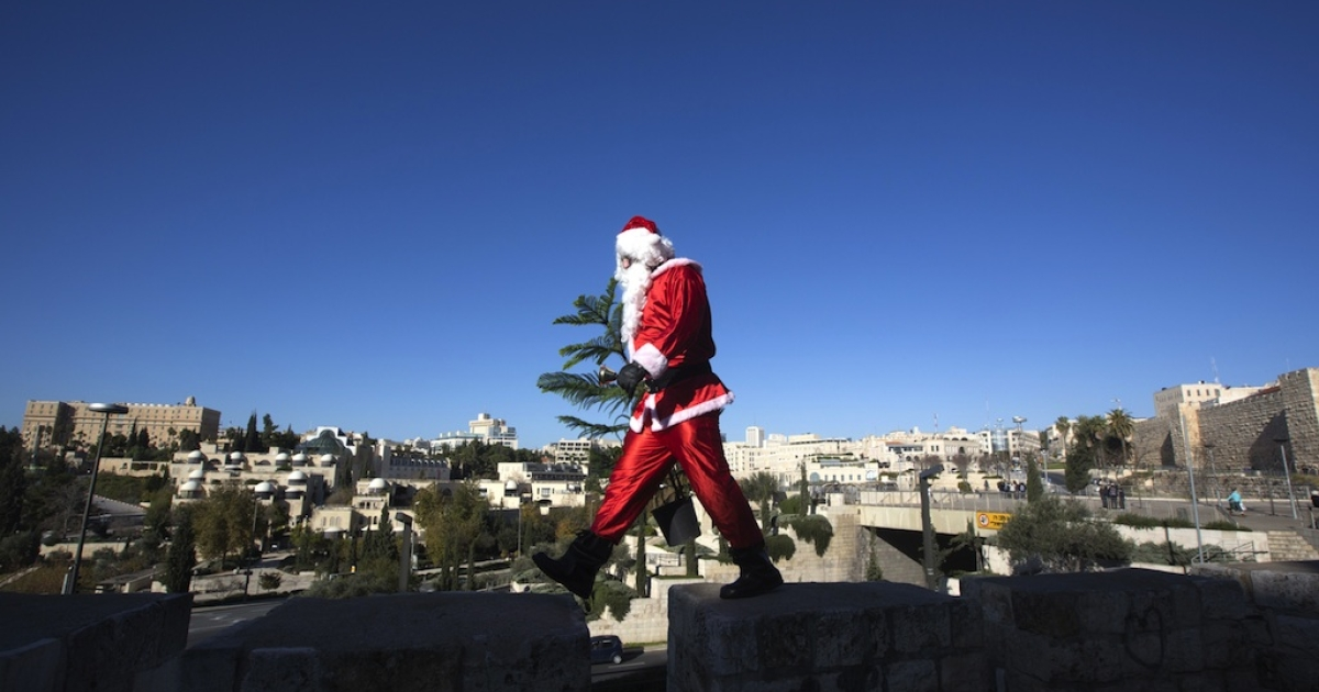 A Palestinian man dressed up as Santa Claus carries a Christmas tree and rings a bell as he walks along the wall of Jerusalem's Old City, on December 23 2012, as Christians around the world prepare for Christmas celebrations.</p>