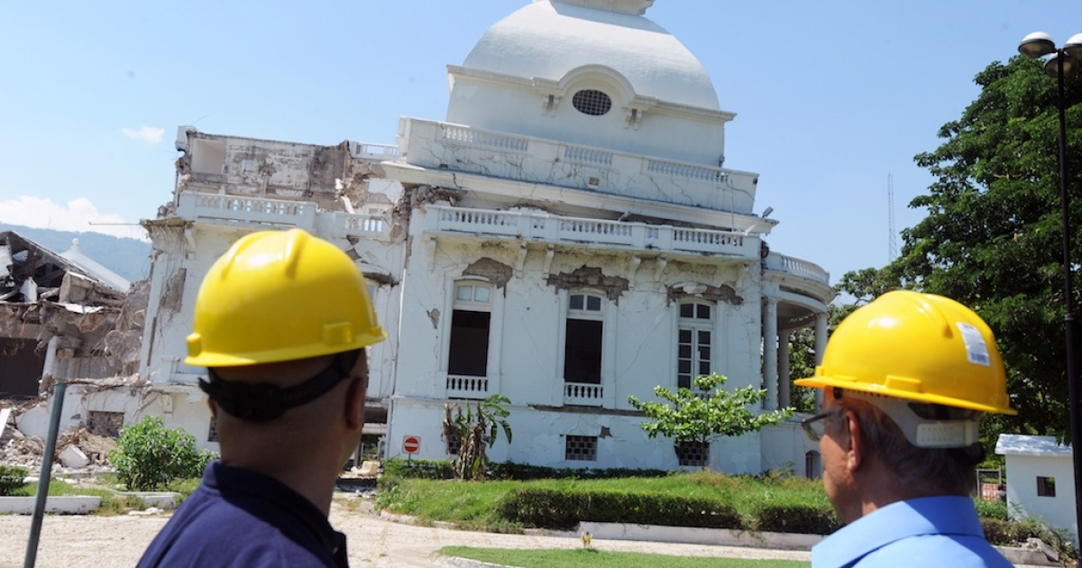 Workers stand in front of the condemned National Palace, on September 7, 2012 in Port-au-Prince. Demolition of the building is now underway.</p>