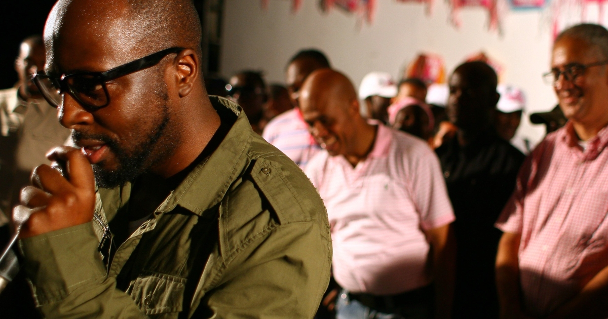 Singer Wyclef Jean attends a rally in support of Haitian presidential candidate Michel Martelly (background, center) in the Petionville suburb of Port-au-Prince on March 16, 2011.</p>