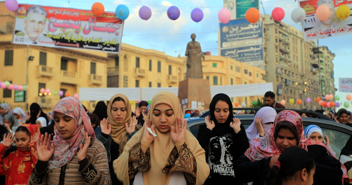 Egyptian Muslim women gather to pray under a statue of the late Egyptian diva Umm Kulthum as they celebrate Eid al-Adha, on the main street the Nile Delta city of Mansura some 120 north of Cairo. Nov. 6, 2011</p>
