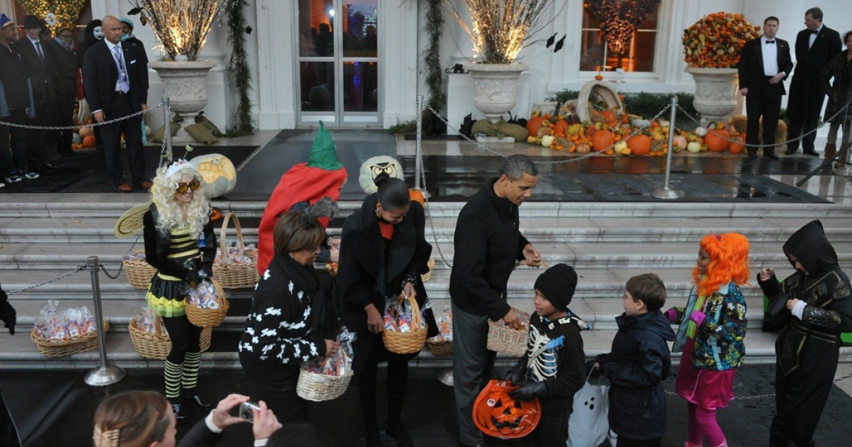 Barack and Michelle Obama welcome trick-or-treaters at the White House. That's candy, not bibles, in the baskets.</p>