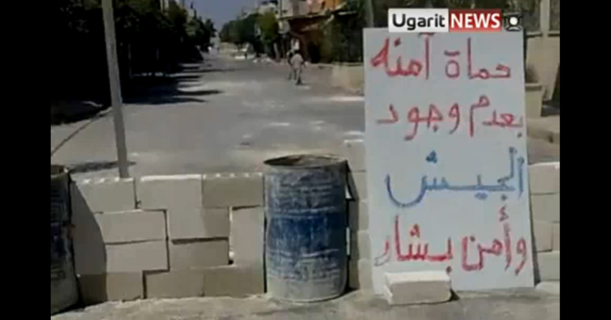 "A make-shift roadblock set up by residents of Hama in an effort to prevent the return of the army and security forces. The sign reads: ""Hama is safe without the presence of Bashar's army or security forces.""</p>"
