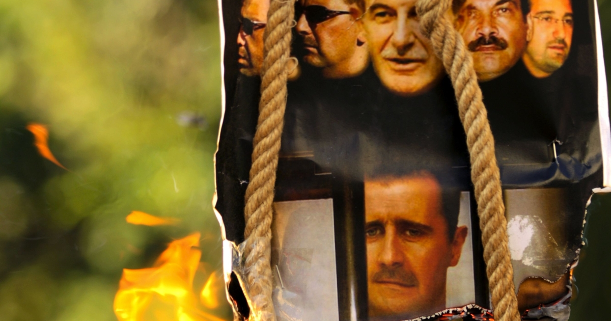 A makeshift gallows with a poster shows the pictures of former Syrian president Hafez al-Assd (top-C), his sons current President Bashar al-Assad (2nd L and bottom C) and Maher (L), their brother in-law General Assef Shawkat (2nd R) and businessman Rami Makhluf (R), during an anti-regime protest outside the Syrian embassy in the Cypriot capital Nicosia on July 31, 2011.</p>