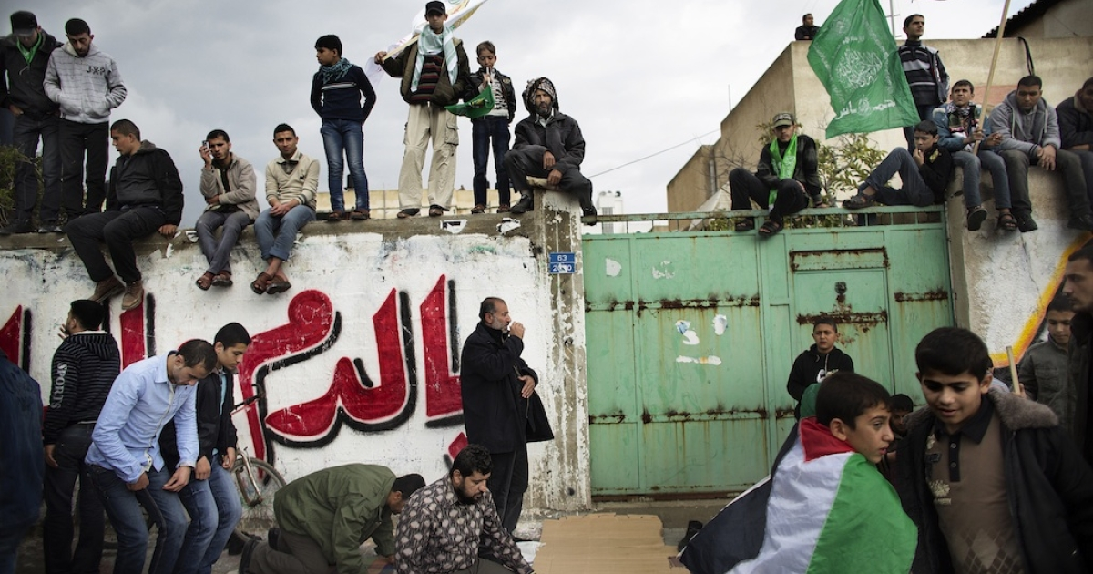 Palestinians pray as others watch on during a rally to mark the 25th anniversary of Hamas in Gaza City on December 8, 2012.</p>