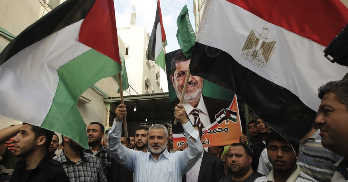 Senior Hamas official Ismail Haniya holds up the Palestinian flag (L) and the Egyptian flag (R) as he celebrates in Gaza City after the Muslim Brotherhood's presidential candidate Mohamed Morsi was declared the winner of the Egyptian elections, on June 24, 2012. Hamas met with Morsi in Egypt last week, which resulted in lifting travel restrictions through the border between Gaza and Egypt.</p>