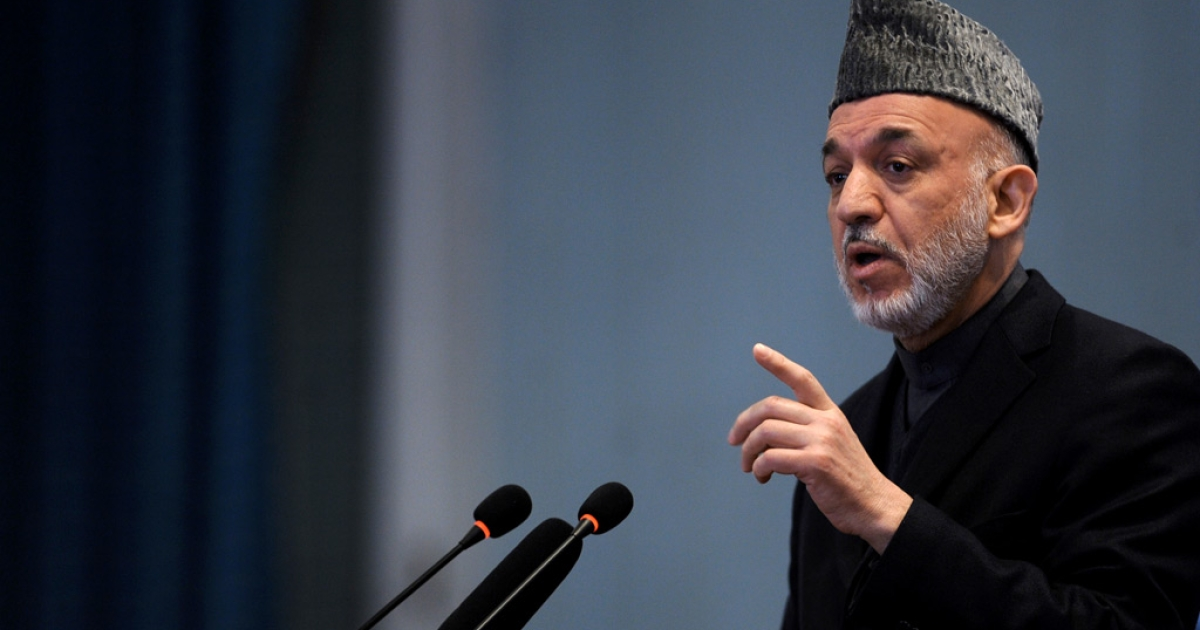 Afghan President Hamid Karzai gestures as he addresses a gathering of women to mark International Women's Day at Amani High School in Kabul on March 8, 2011.</p>