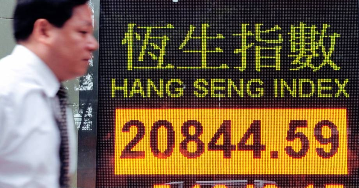 A man walks past a display board showing the Hang Seng Index in Hong Kong on August 5, 2011. Hong Kong shares dived more than five percent amid a worldwide sell-off.</p>