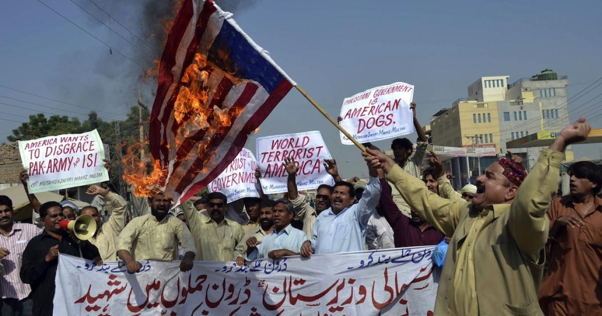 A Pakistani protester holds a burning US flag as others shout slogans during a protest in Multan on October 31, 2011 against US drone attacks in the Pakistani tribal region. Relations between Pakistan and the United States deteriorated after the May 2, 2011 killing of Al Qaeda leader Osama bin Laden by US Navy SEALs in Abbottabad, Pakistan, and again over accusations that Pakistani intelligence was involved with the Haqqani network.</p>
