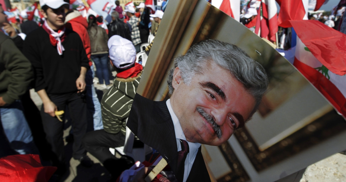 A man holds a picture of Lebanese slain Prime minister Rafic Hariri as he takes part in a mass rally gathering tens of thousands opposition supporters marking the sixth anniversary of a popular uprising against Syrian troops in Lebanon, demanding the disarming of Hezbollah, on March 13, 2011 in central Beirut.     AFP PHOTO / JOSEPH EID (Photo credit should read JOSEPH EID/AFP/Getty Images)</p>
