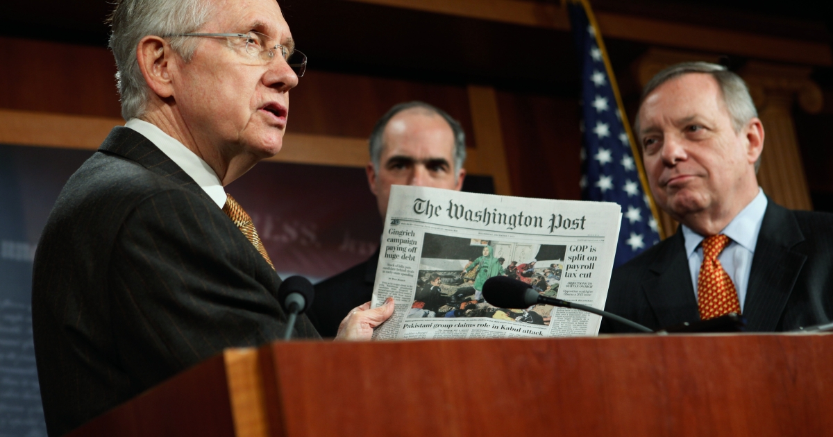 Senate Majority Leader Harry Reid (L) holds up a copy of today's Washington Post during a news conference about extending the payroll tax cut with US Sen. Robert Casey and Senate Majority Whip Richard Durbin at the US Capitol on Dec. 7, 2011.</p>