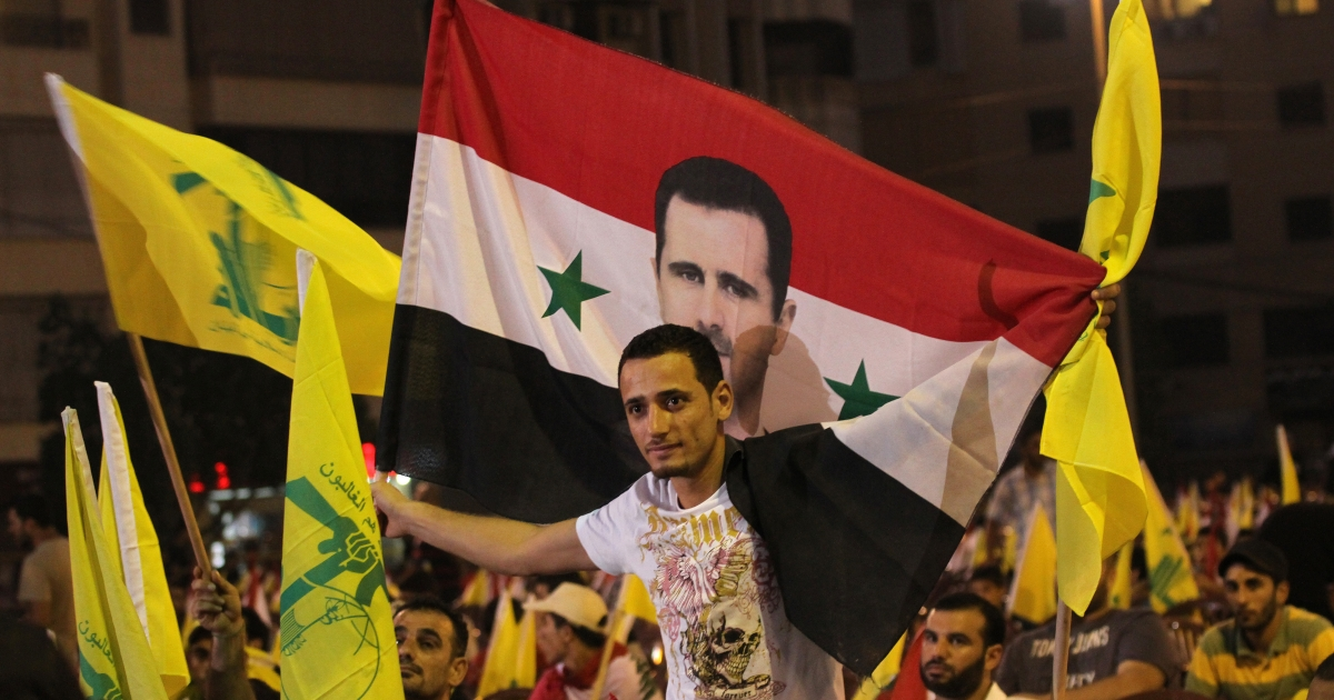 Lebanese Hezbollah supporters wave the movement's yellow flags and hold up the Syrian flag decorated with an image of President Bashar al-Assad as they listen to a televised speech by Hezbollah chief Hassan Nasrallah to mark the sixth anniversary of the 2006 war with Israel in southern Beirut on July 18, 2012.</p>