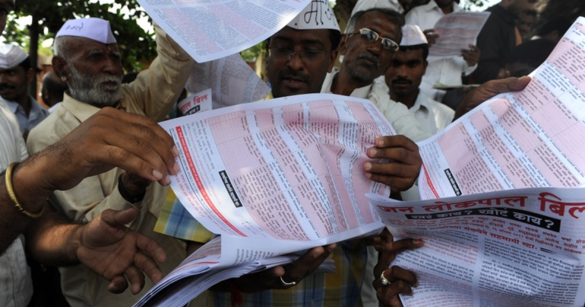 Supporters of hunger-striking activist Anna Hazare grab pamphlets explaining the anti corruption bill