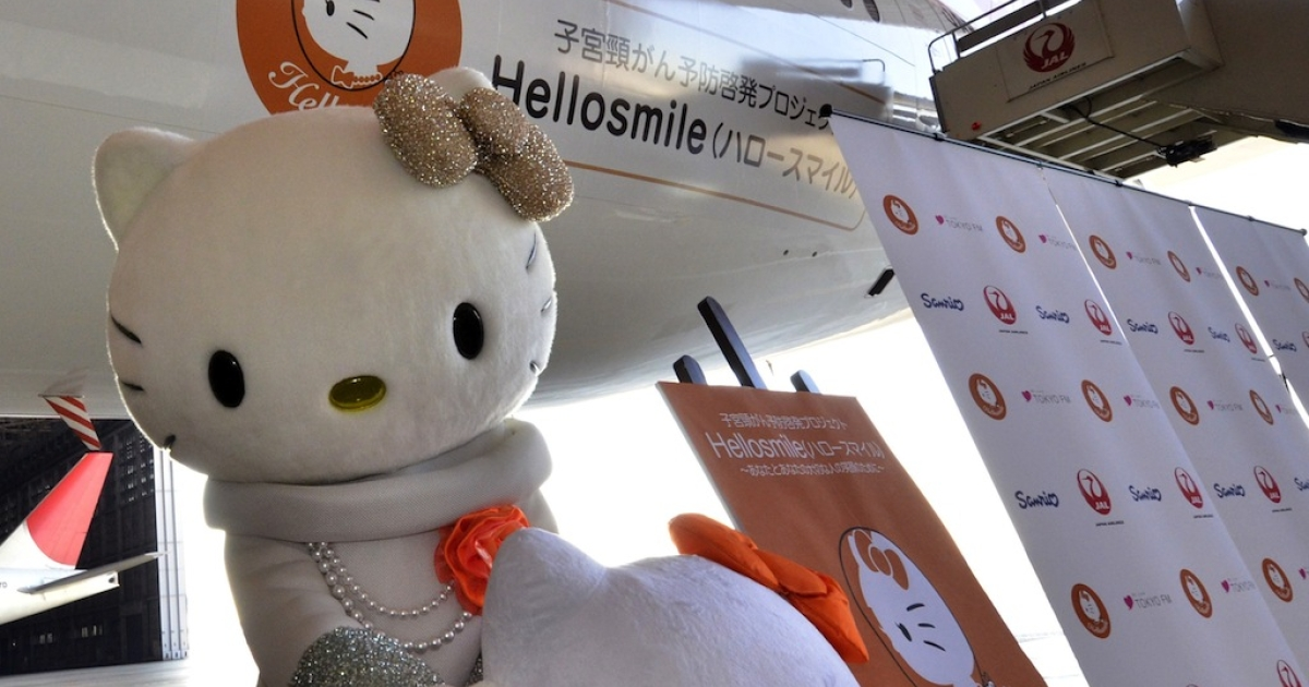 Japan Airlines (JAL) cabin attendants and Sanrio character Hello Kitty introduce JAL's Hellosmile jet, a Boeing 777 jetliner painted with a Hello Kitty face to raise awareness of cervical cancer, at JAL's hanger at the Haneda Airport in Tokyo on January 13, 2012.</p>