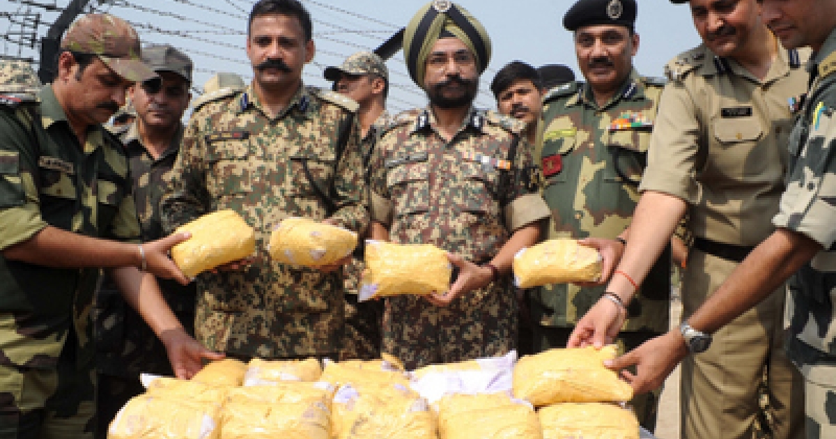 Indian Border Security Force (BSF) Additional Director General (ADG) Himmat Singh (C), BSF Deputy Inspector General (DIG) Sanjeev Bhanot (3R) BSF 41 Battalion Commandant Ish Aul (2L) along with BSF personnel pose with 27 kilogrammes of confiscated heroin during a press conference held close to The India-Pakistan Border at Rajatal, some 40kms from Amritsar on October 6, 2011.  Singh said that BSF personnel recovered the drugs after an encounter with alleged miscreants close to the border between the South Asian neighbours a haul of nine bundles of narcotics with each containing 3 packets,  total 27 packets . The narcotics were allegedly smuggled into the country from neighbouring Pakistan, officials said.</p>