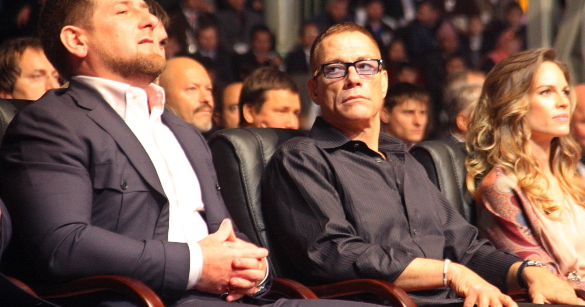 Belgian actor Jean-Claude Van Damme (C) looks at Chechen leader Ramzan Kadyrov (R) as they watch, with Hilary Swank (R), a performance in Grozny late on October 5, 2011.</p>