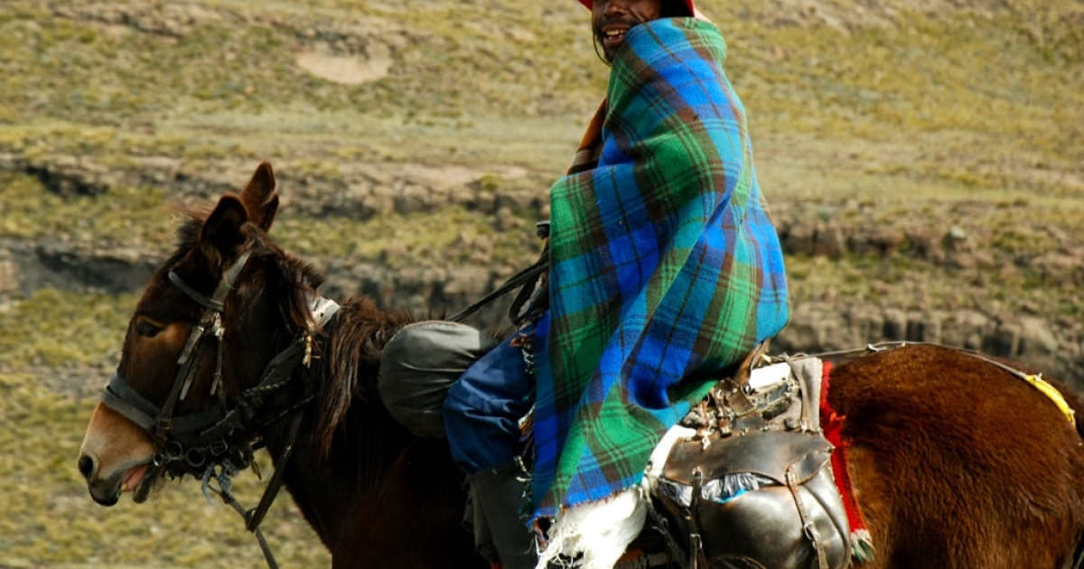 A Lesotho man on horseback in the mountainous country.</p>