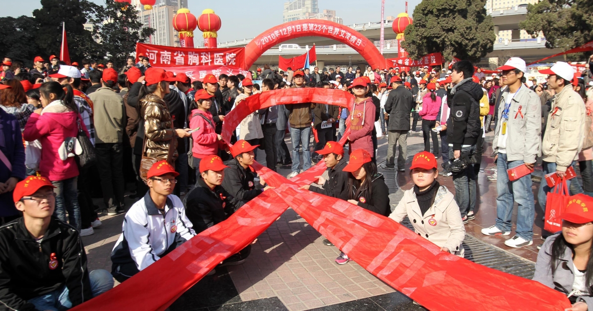 AIDS activists gather to form a red ribbon, marking the World's AIDS day in Zhengzhou, central China's Henan province on December 1, 2010. A retired senior Chinese health official Chen Bingzhong, 78, who has advanced liver cancer, called for two of the country's most powerful leaders to take responsibility for a huge 1990s blood-selling AIDS scandal in Henan province. CHINA OUT AFP PHOTO</p>