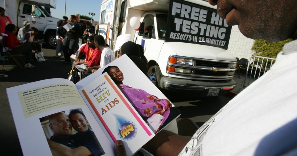 A man reads education literature as he waits for an HIV test at a free mobile testing center in Los Angeles.</p>