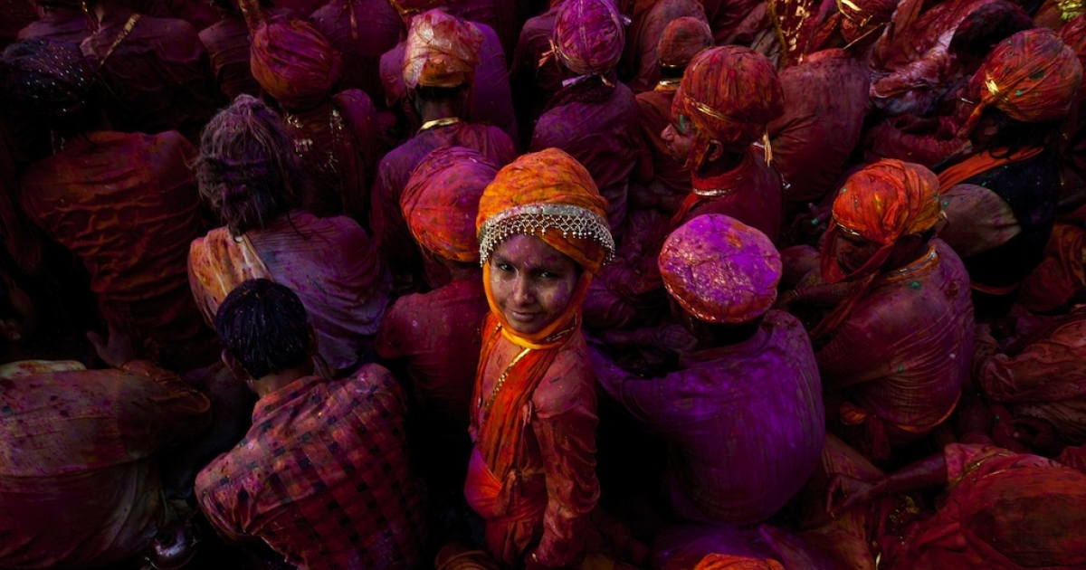 A child looks on as Indian villagers smear themselves with colors during the Lathmar Holi festival at the Nandji Temple in Nandgaon, some 120 kms from New Delhi, on Mar. 3, 2012.</p>