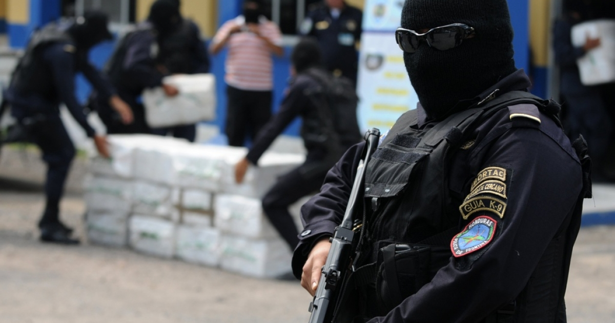 Members of the police drug squad guard at least 400 kilos of cocaine seized in the Mosquito Coast of Honduras, on May 7, 2012.</p>