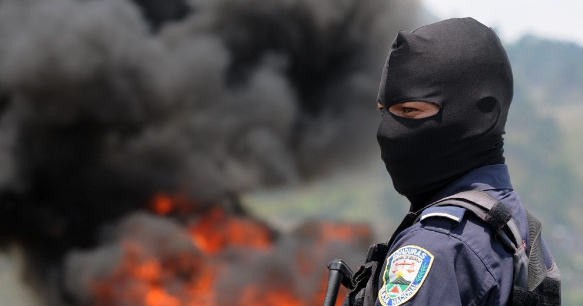 A Honduran policeman stands guard as about 400 kilograms of cocaine are aflame in Tegucigalpa on May 11. The drugs were seized as part of a joint operation with US Special Forces.</p>