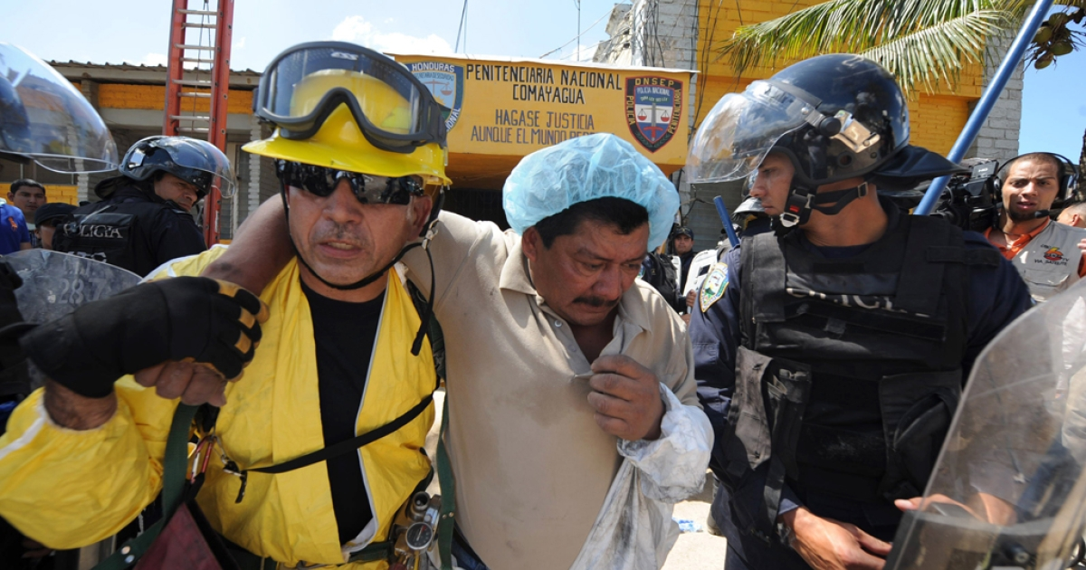 A forensic technician who got intoxicated by the fumes (C) is helped by firefighters to leave the National Prison compound in Comayagua, Honduras,  on February 15, 2012, where almost 300 prisioners were killed and scores injured when a fire overnight tore through the prison in central Honduras. The prison held around 850 prisoners.   AFP PHOTO/ORLANDO SIERRA (Photo credit should read ORLANDO SIERRA/AFP/Getty Images)</p>