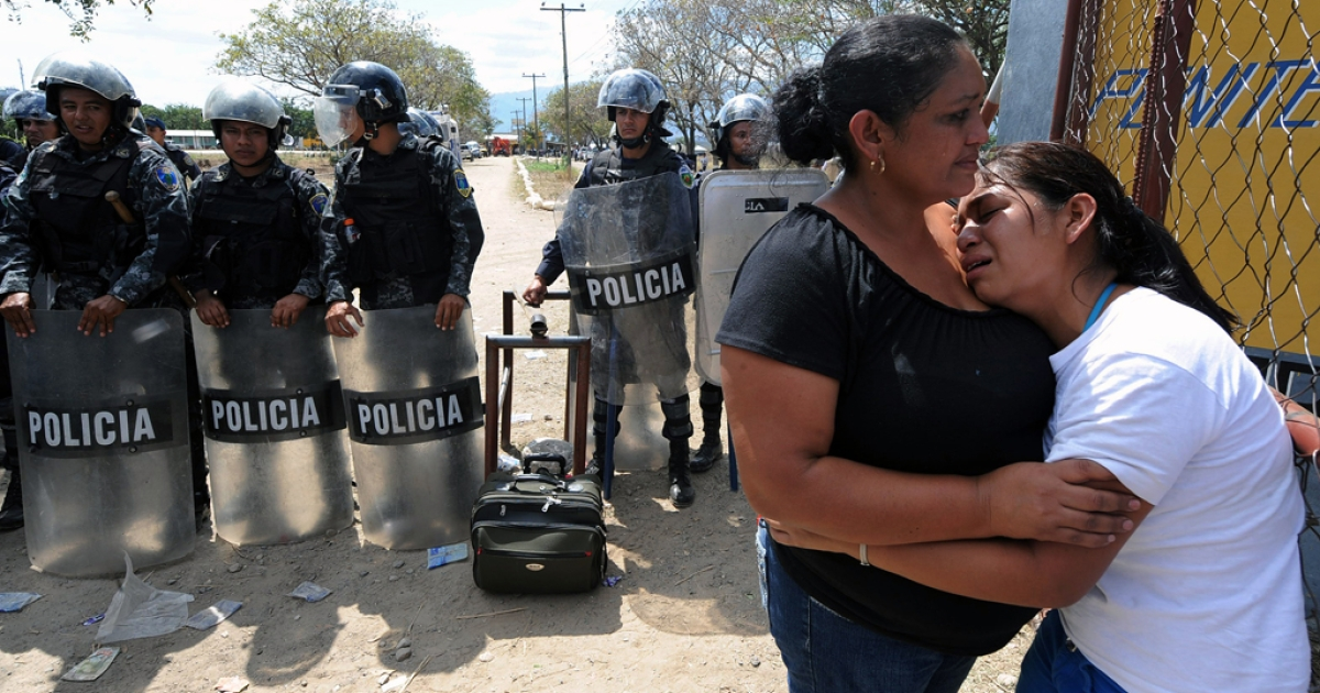 Two women, relatives of victims, mourn for their beloved, outside the National Prison compound in Comayagua, on February 15, 2012, following a fire overnight which tore through the prison in central Honduras. A fire swept through the Honduran prison killing at least 272 inmates, officials said, warning the toll could rise with many inmates left trapped in their cells by the fierce inferno.     AFP PHOTO/Orlando SIERRA (Photo credit should read ORLANDO SIERRA/AFP/Getty Images)</p>