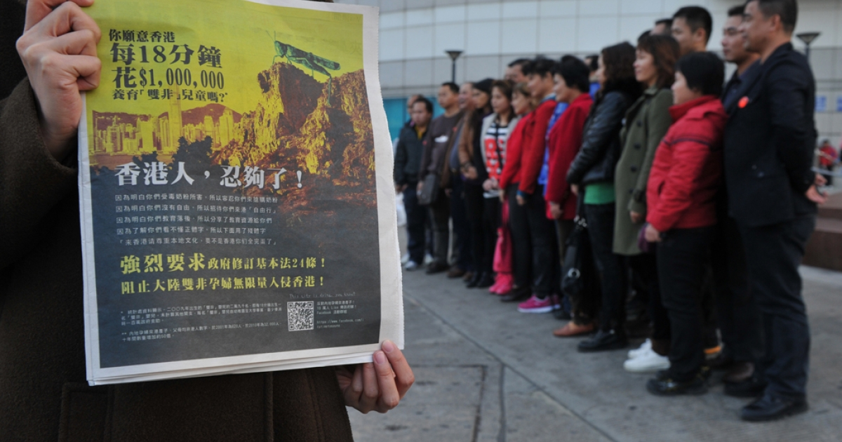 A girl holds a Hong Kong newspaper with an anti-mainland China advertisement with a picture of a locust looking over the Hong Kong cityscape on Feb. 1, 2012.</p>